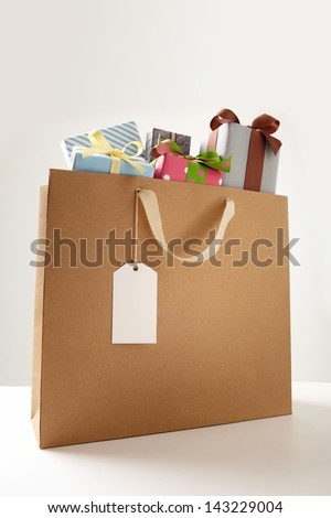 Shopping Bag of presents on white table.  brown Shopping bag. - stock photo