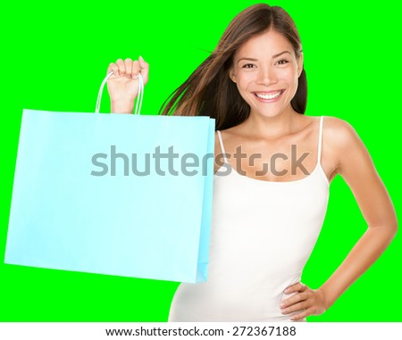 Shopping bag woman. Beautiful smiling happy woman holding showing blue shopping bag isolated cutout on green chroma key background. Fresh multiracial Asian Caucasian female model. - stock photo