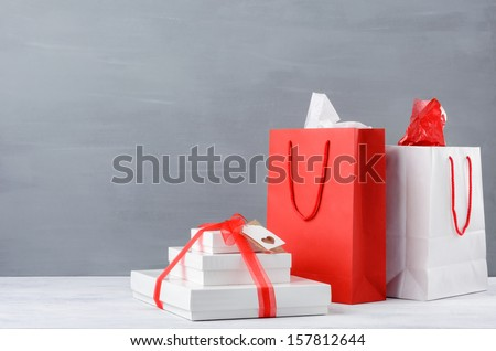 Shopping bags and gift boxes or presents on table top, on grey background with plenty of copy space christmas xmas seasonal holiday - stock photo