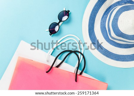 Shopping bags and sunglasses with hat on blue background - stock photo