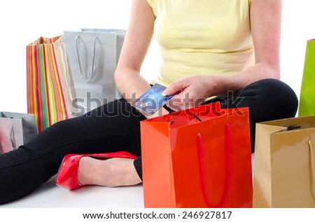 Shopping bags around a woman holding a credit card, isolated on white