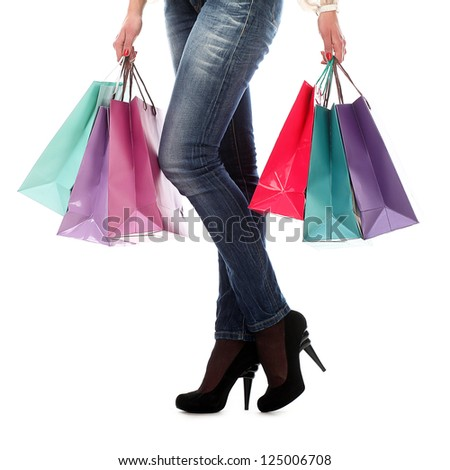 Shopping bags near legs in jeans and high heels over white background - stock photo