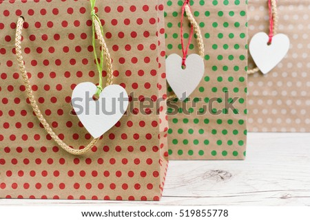 Shopping bags with label of heart on a white wooden background, closeup
