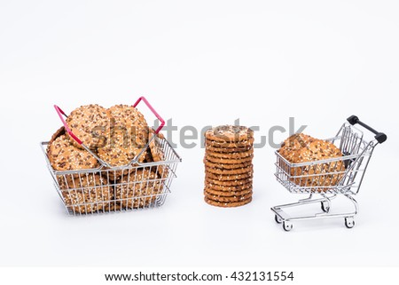 Shopping basket full of cookies and wire trolley with tasty cookies, and tower of cookies with flax and sesame seeds, isolated with white background  - stock photo