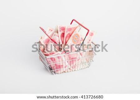 Shopping basket or cart full of Yuan - currency. Symbolic example of spending money in shops, or advantageous purchase in the shopping center. Yuan notes from China's currency. Chinese banknotes - stock photo