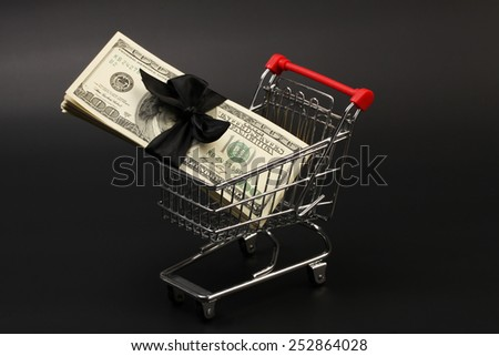 Shopping basket with stack of money american hundred dollar bills with black bow inside standing on black background - stock photo