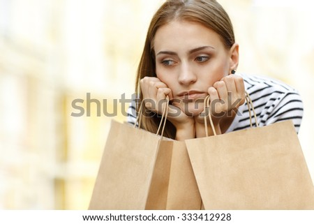 Shopping can be tiring. Close up horizontal portrait of a young shopper holding her bags looking exhausted - stock photo