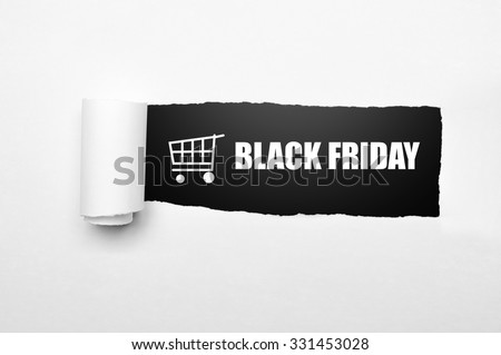 Shopping cart and black friday text on paper tear. Black friday concept - stock photo