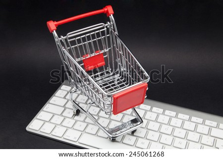 shopping cart and computer on black keyboard - stock photo