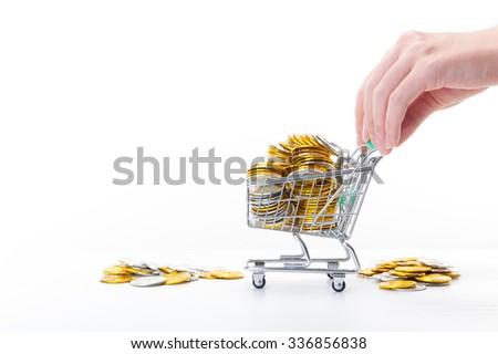 Shopping cart and gold coins - stock photo