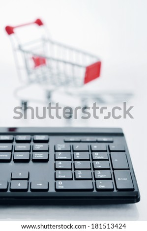 Shopping cart and keyboard on light background - stock photo