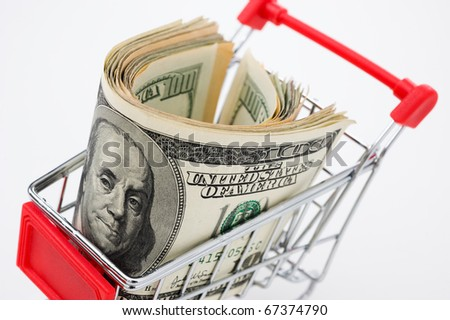 Shopping cart and stocks of dollars close up shot. - stock photo
