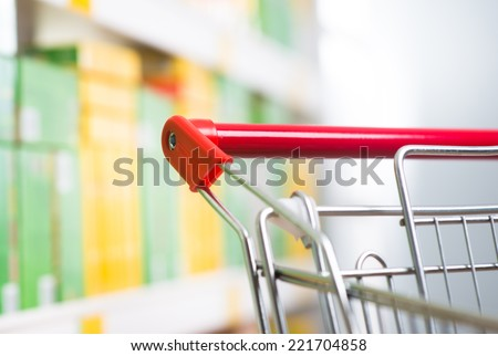 Shopping cart detail close-up with store shelf on background. - stock photo