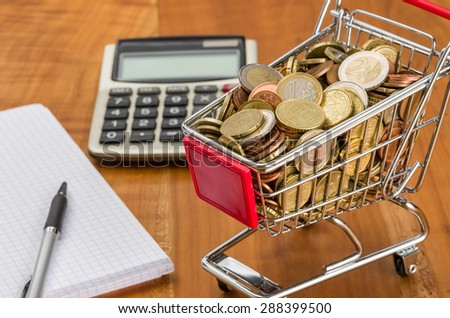 Shopping cart filled with coins on a wooden desk - stock photo