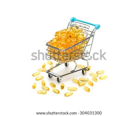 Shopping cart filled with yellow omega 3 fatty acids capsules on pure white background with some fallen out. Healthy shopping and lifestyle concept. - stock photo