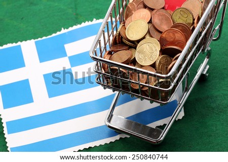Shopping cart full of coins euro over Flag of Greece - stock photo