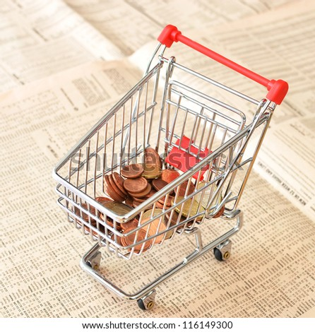 Shopping cart full of euro cents in a financial newspaper - stock photo