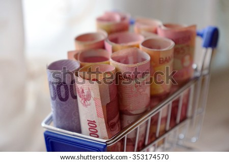 Shopping cart full of money (indonesia rupiah). Multi currency basket concept. SOft focus and selective focus of image - stock photo