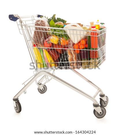 Shopping cart full with dairy grocery products isolated over white background - stock photo