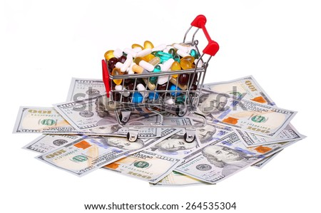Shopping cart full with pills and capsules over dollar bills isolated on white