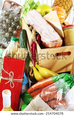 Shopping cart full with various groceries, close-up - stock photo