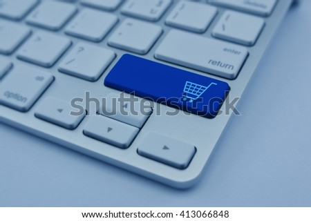 Shopping cart icon on modern computer keyboard button, Shopping online concept, blue tone - stock photo