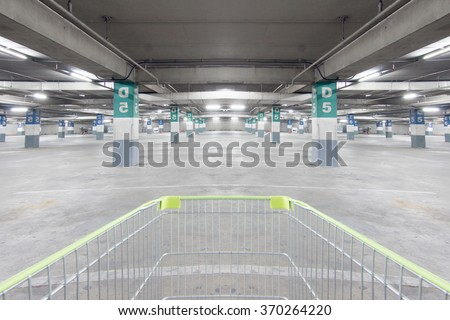 shopping cart in a parking of supermarket garage without any car - stock photo