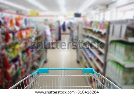 shopping cart in convenience store shelves blurred background - stock photo