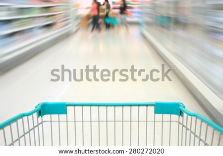 shopping cart in supermarket aisle motion blur - stock photo