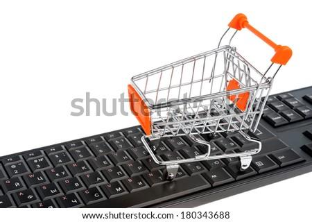 Shopping cart on black keyboard isolated on white background - stock photo