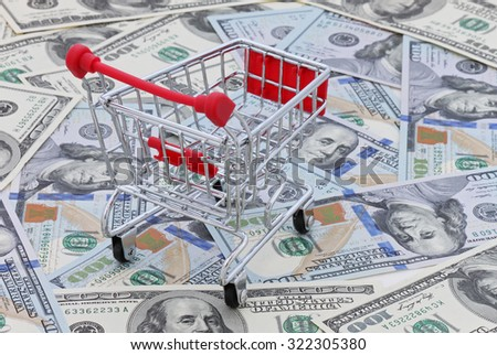 shopping cart on heap of 100 dollars banknotes