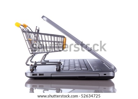 shopping cart over a laptop isolated on white with reflection - stock photo