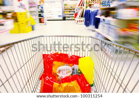 shopping cart standing between shelves in the supermarket - stock photo