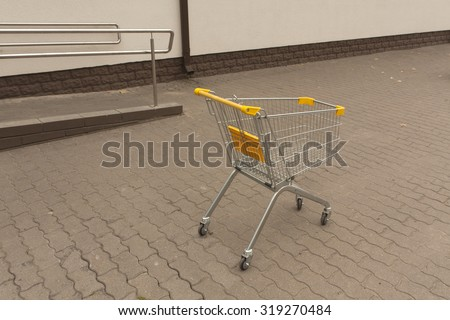 Shopping cart trolley standing outside. Urban background - stock photo