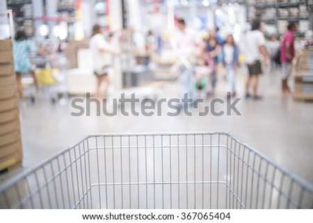 Shopping cart view with Blurred background of big retail store and people walking shopping