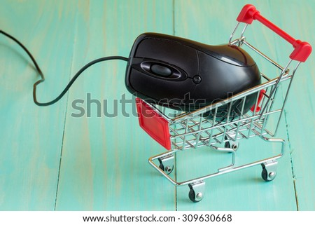 Shopping cart with a computer mouse on blue background - stock photo