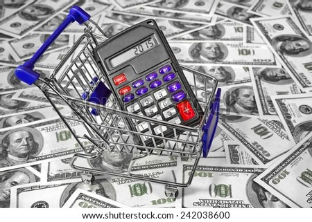 Shopping Cart with Calculator and 2015 sign on the Display and  US Dollars Bills in the Background