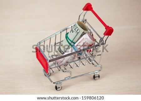Shopping cart with dollars and euros inside, on ceramic background - stock photo