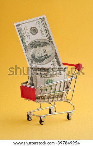 Shopping Cart With Dollars On Yellow Background