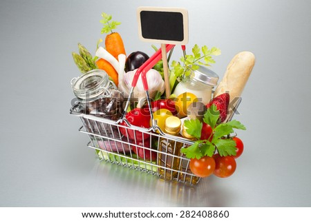 Shopping cart with food and marker prices - stock photo