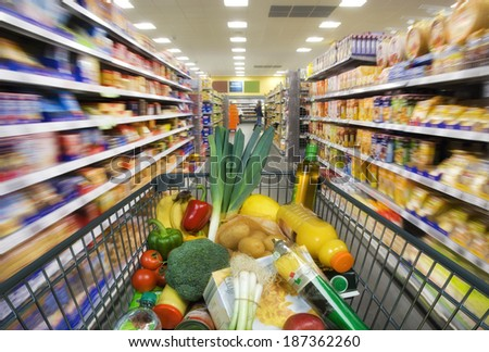 Shopping cart with foods between store shelves in a supermarket. - stock photo