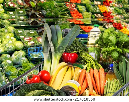 Shopping cart with fruit and vegetables in the supermarket.