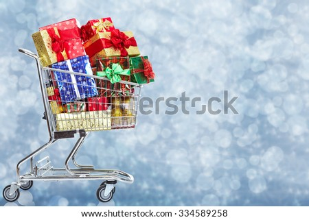 Shopping cart  with gifts over Christmas background. - stock photo