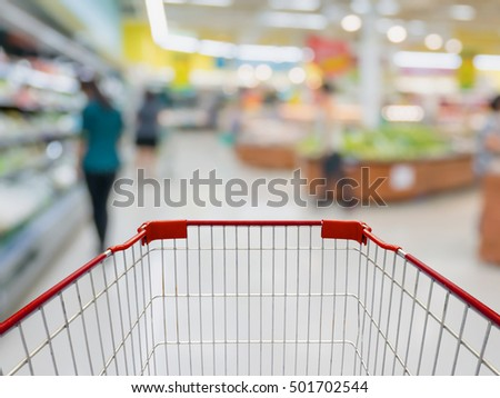 Shopping cart with Grocery store blur background with customers
