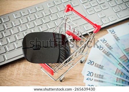 Shopping cart with mouse in front of  keyboard ,online shopping concept - stock photo