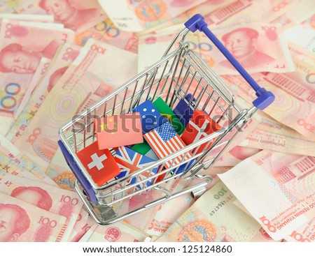 shopping cart with national flag on a lot of Renminbi on white background - stock photo