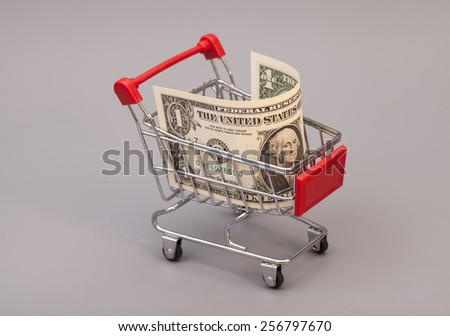 Shopping cart with one dollars on gray background - stock photo