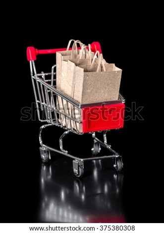 shopping cart with paper bags is isolated on black background - stock photo