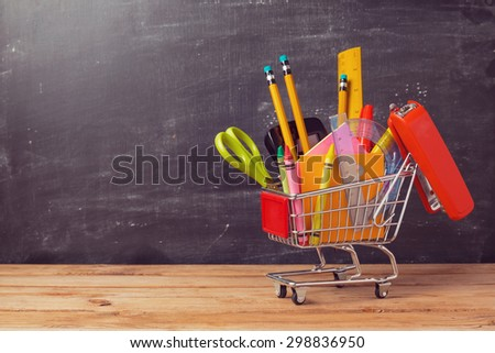 Shopping cart with school supplies over chalkboard background. Back to school sale concept - stock photo