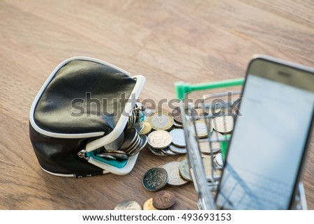 Shopping cart with wallet, coins and phone on the wooden surface
